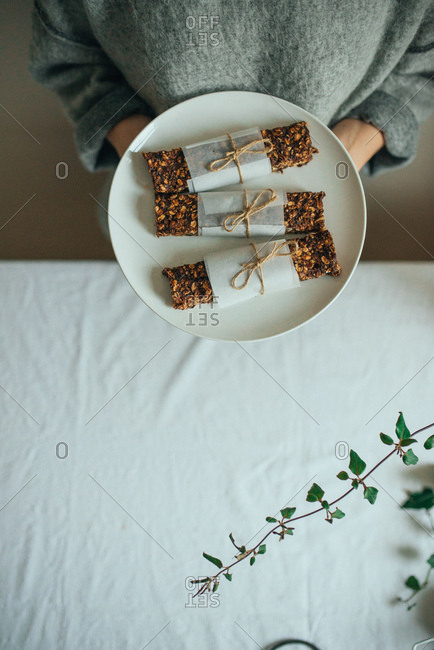 Woman holding a plate of homemade granola bars