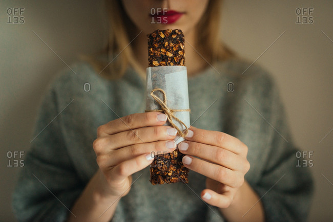 Woman holding a paper and twine wrapped homemade granola bar