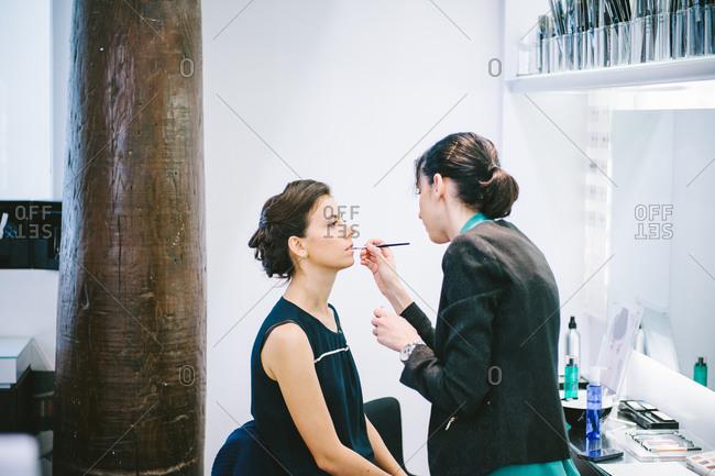 Strasbourg, France - August 30, 2014: Make up artist putting makeup on bride's lips for wedding