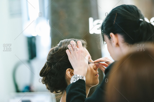 Young woman having a professional do her make-up before the wedding