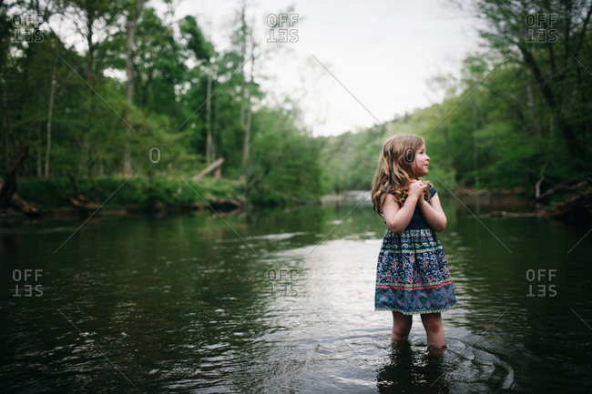 A little girl standing in river