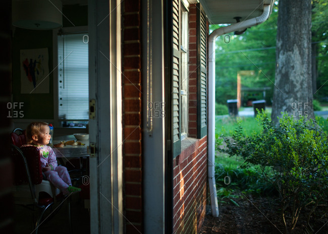A little girl watching the sun rise from kitchen window