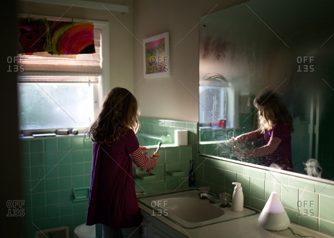 A little girl holding a toothbrush in the bathroom