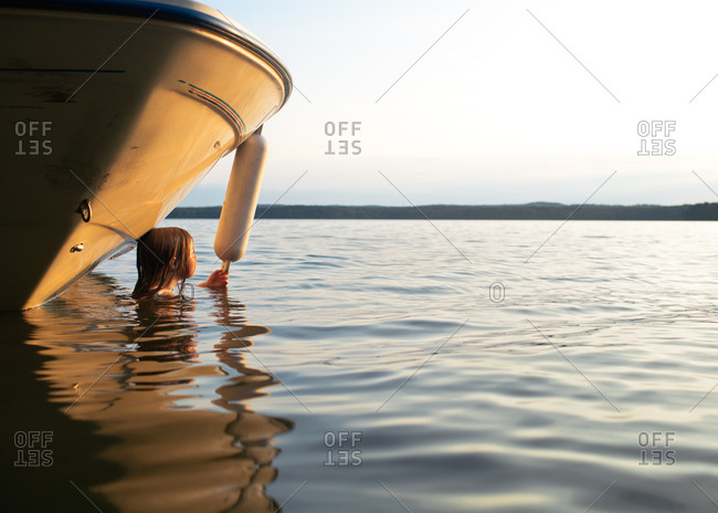 A girl floating next to boat