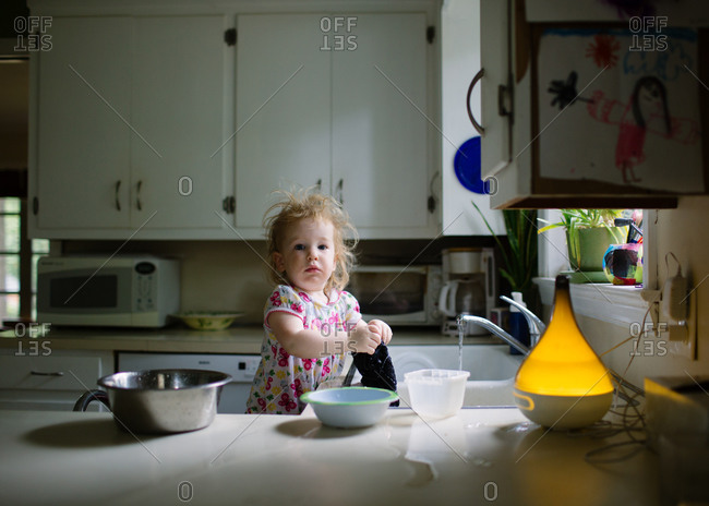 A toddler girl helps wash dishes