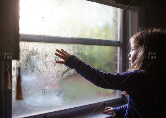 Little girl writing in condensation on a window