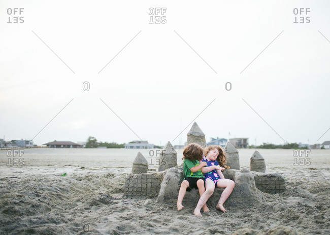 Kids sitting on the beach next to sand castle