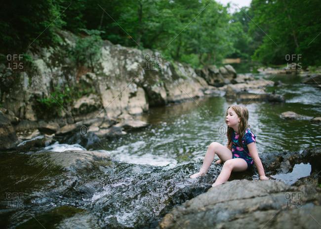 Girl sitting in a stream