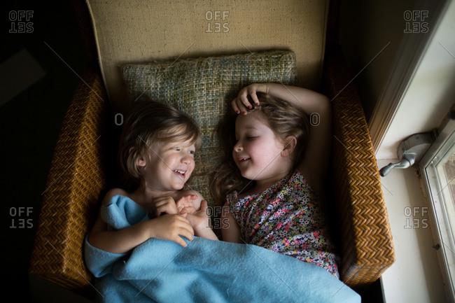 Siblings lying in chair laughing