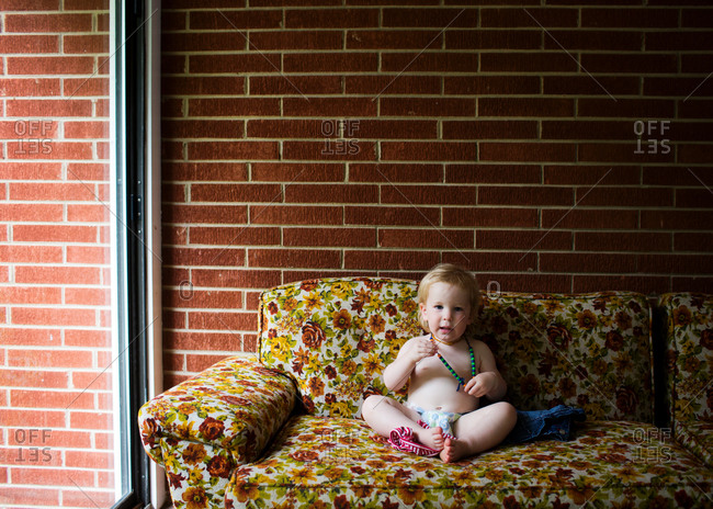 Baby girl sitting on a floral couch in a diaper