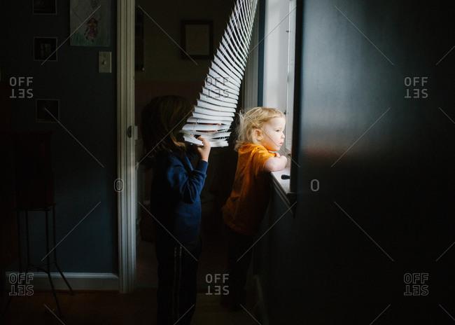 Siblings looking out of window