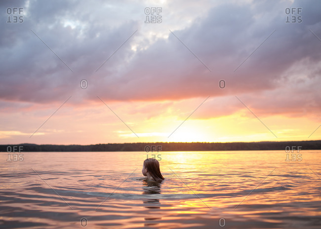 A girl swimming at sunset
