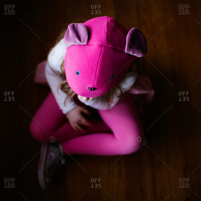 A girl in a pink animal hat sitting on the floor