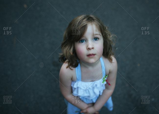 A little girl looking up with hands clasped