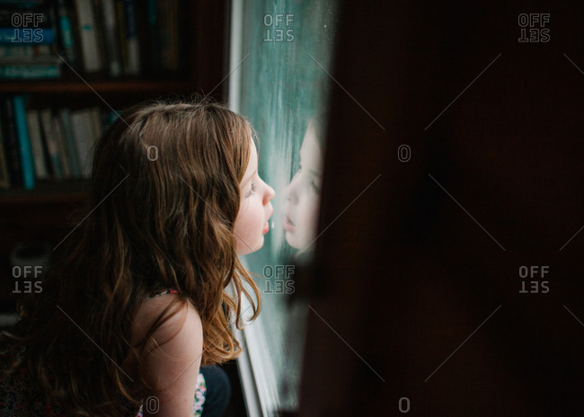 A girl creating condensation on a window