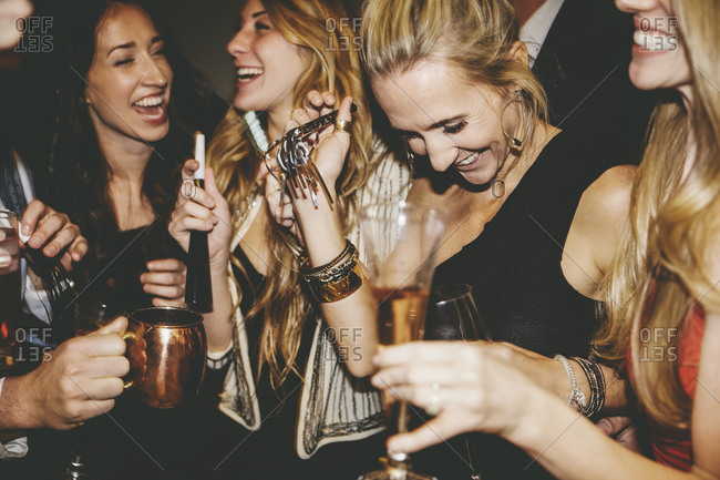 Friends laughing and holding noisemakers at a party