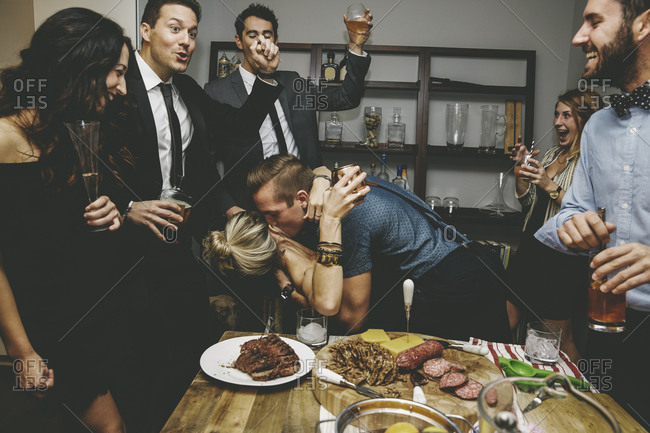 Man and woman being cheered on by their friends as they kiss at a party
