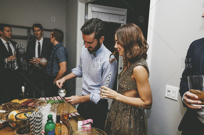 Friends standing at a table at a party fixing cocktails