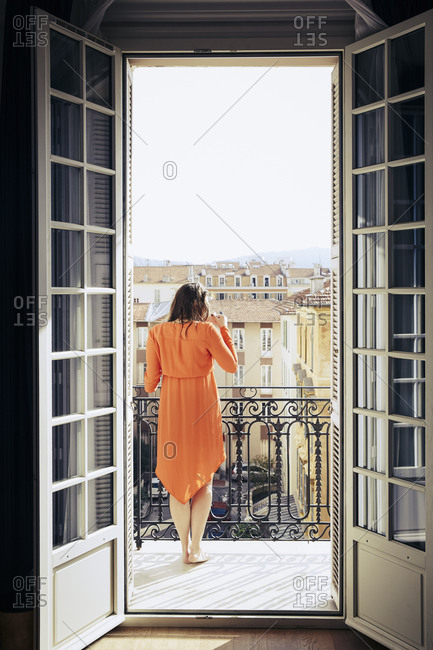 Woman standing on a balcony drinking coffee