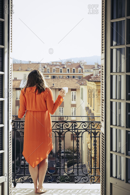 Woman standing on a balcony overlooking rooftops with a cup of coffee