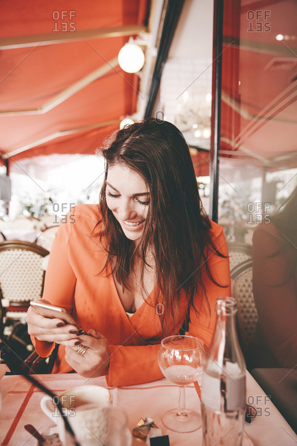 Woman sitting at an outdoor cafe table checking her phone