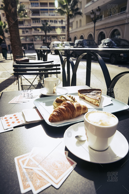 Coffee, pastries and playing cards on an outdoor cafe table