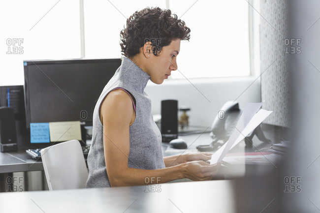 Woman reviewing documentation in cubicle