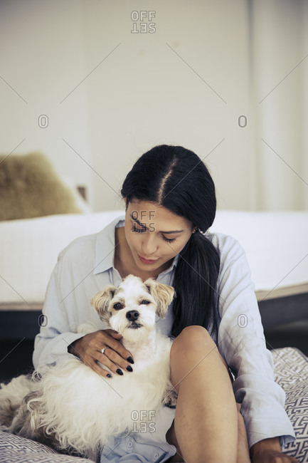 Woman cuddling with a dog on a cushion in a bedroom