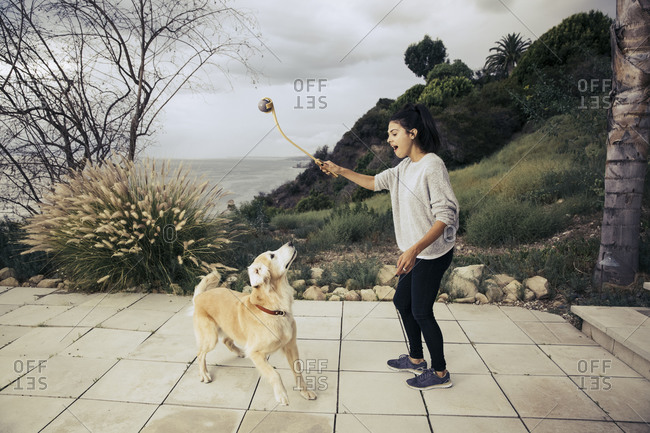 Woman standing on a patio playing ball with her dog