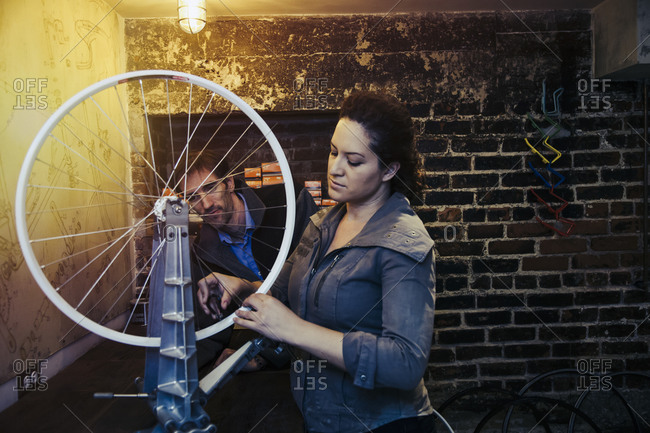 Man and woman working on a bicycle tire in a repair shop