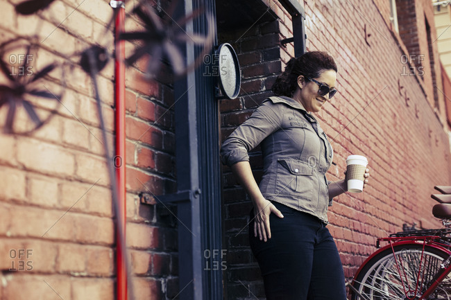 Woman standing at the entrance to a bicycle repair shop with a cup of coffee