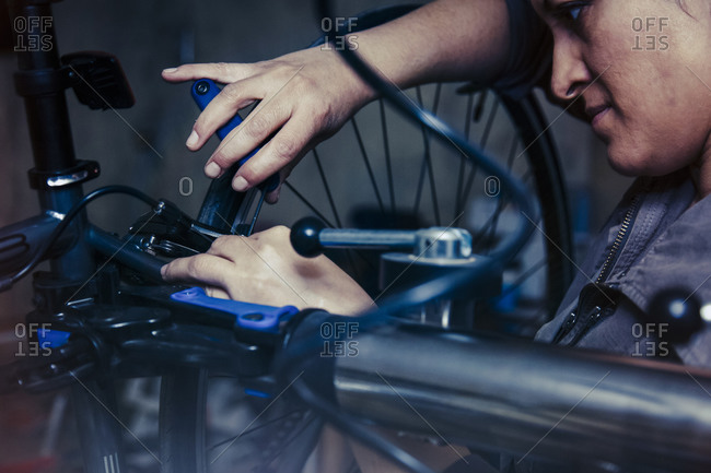Woman working on a bicycle in a repair shop