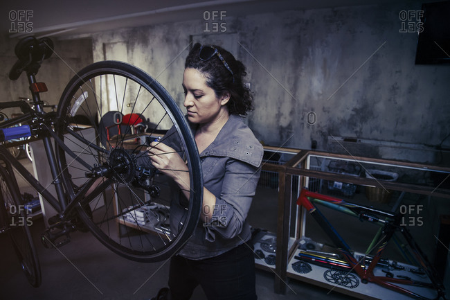 Woman standing a repair shop working on a bicycle