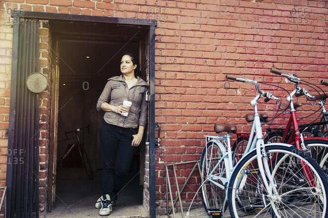 Woman standing in the doorway to a bicycle repair shop with a cup of coffee