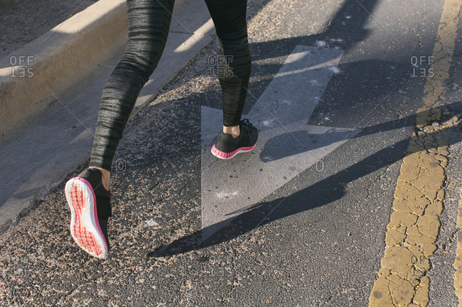 Close-up of woman\'s shoes as she is running on the street