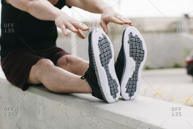 Person wearing running shoes touching toes while stretching to prepare to go for a run