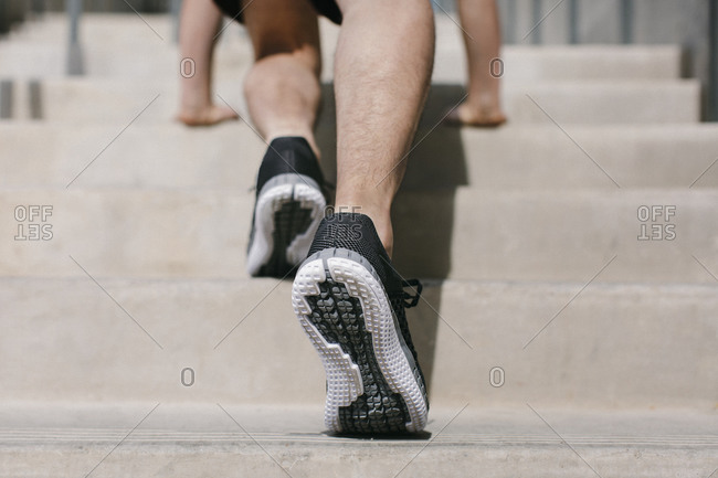 Person wearing running shoes doing stretches on stair in preparation for a run