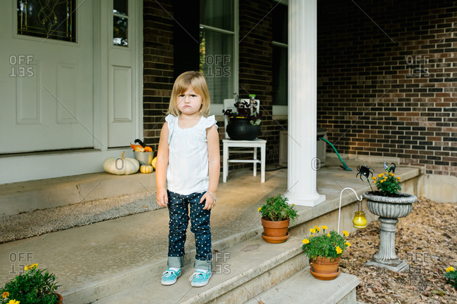 Pouting young girl standing on front porch