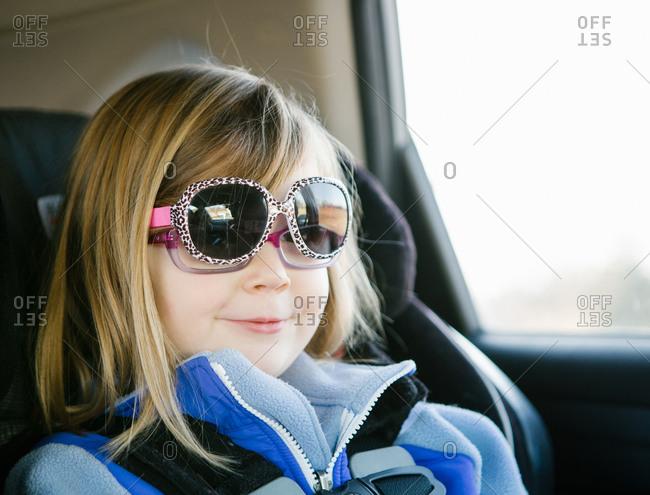 Little girl in car seat wearing sunglasses over her eyeglasses stock ...