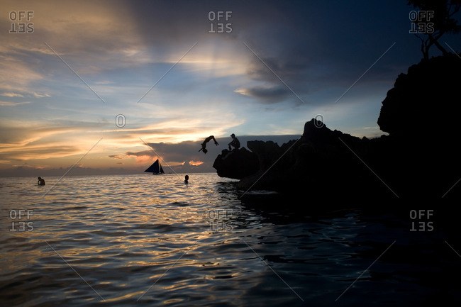 Silhouette of boy doing a backflip off rock into the ocean at Boracay, the Philippines