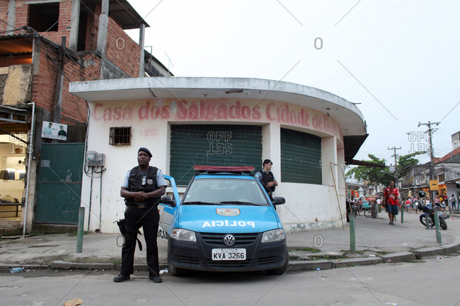 Police officers and stand with their vehicle on street corner in a favela
