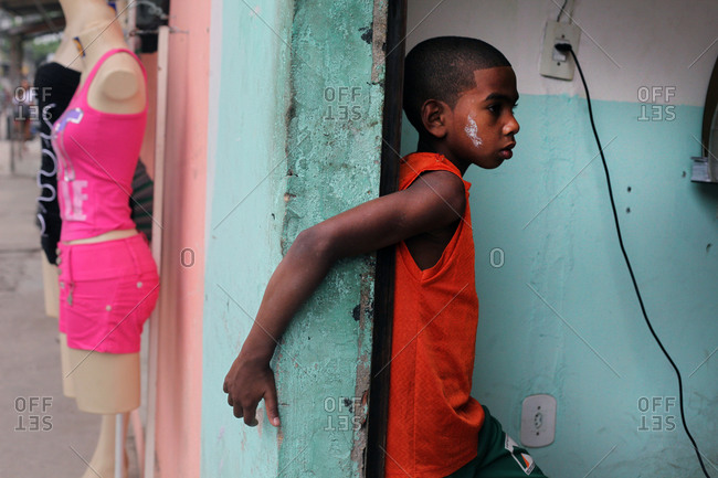 Young boy hangs out at barbershop in the neighborhood of Cidade de Deus