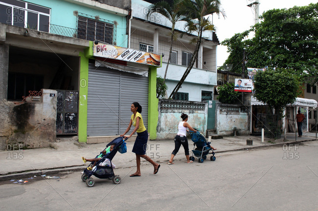 Mothers pushing children inn strollers in the Cidade de Deus neighborhood