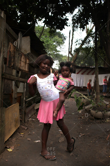 A young girl and her sister pose for a portrait in the neighborhood of Cidade de Deus