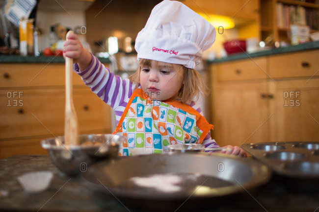 Toddler girl pretending to cook in the kitchen