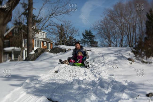 Toddler girl riding a sled with her father