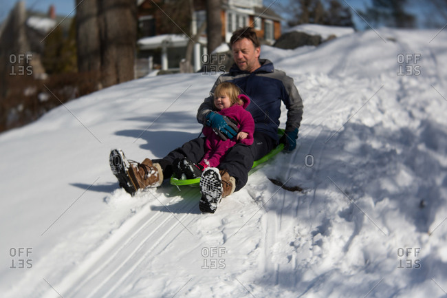 Father sledding with his toddler daughter