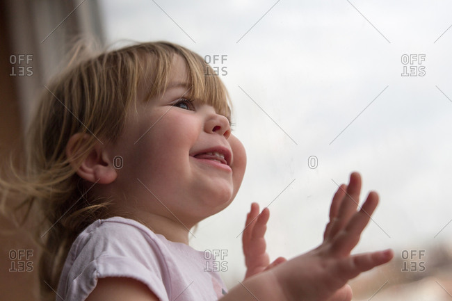 Smiling toddler girl looking out window