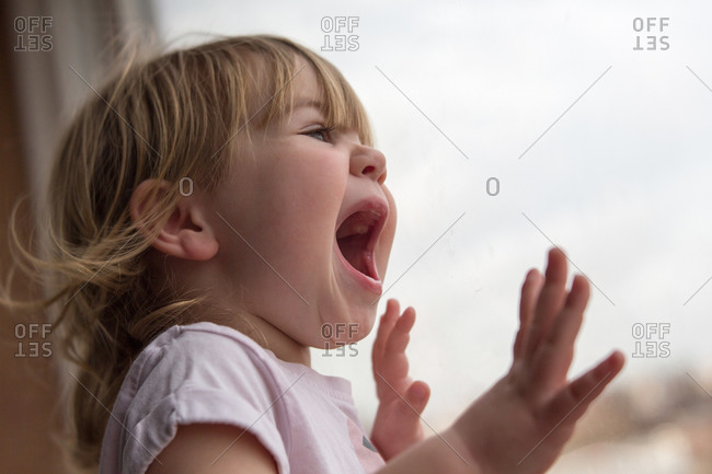 Excited toddler girl looking out window