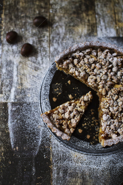 Gluten free tart with candied apples and walnuts topped with sugar sliced